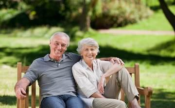 Older couple sitting on bench smiling l Dental Implants Concord NH