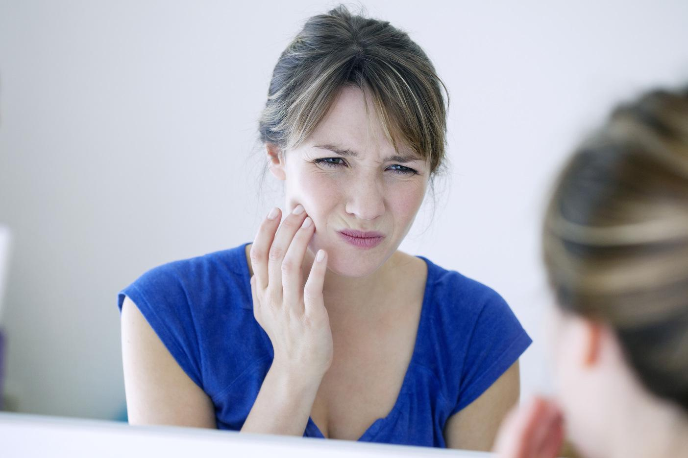 a woman holds her jaw in the mirror | concord nh dentist