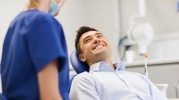 A man smiles up at a dental hygienist | Concord, NH dentist